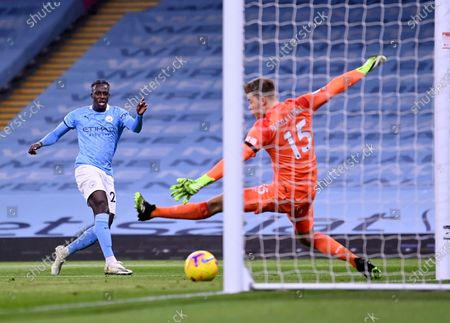 Manchester City's Benjamin Mendy, left, scores his side's third goal during the English Premier League soccer match between Manchester City and Burnley at the Etihad stadium in Manchester, England