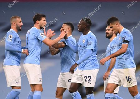 Manchester City's Benjamin Mendy celebrates with teammates after scoring his side's third goal during the English Premier League soccer match between Manchester City and Burnley at the Etihad stadium in Manchester, England