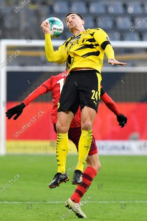 Dortmund's Thomas Meunier jumps for a header during the German Bundesliga soccer match between Borussia Dortmund and 1.FC Cologne in Dortmund, Germany