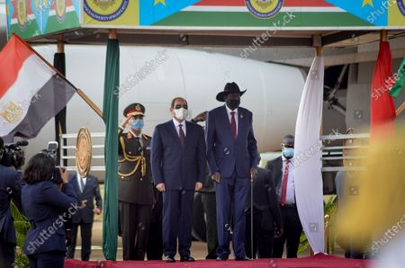 Egypt's President Abdel-Fattah el-Sissi, center-left, and South Sudan's President Salva Kiir, center-right, stand for national anthems after el-Sissi's arrival at the airport in the capital Juba, South Sudan . The Egyptian president is on a one-day visit to discuss bilateral relations