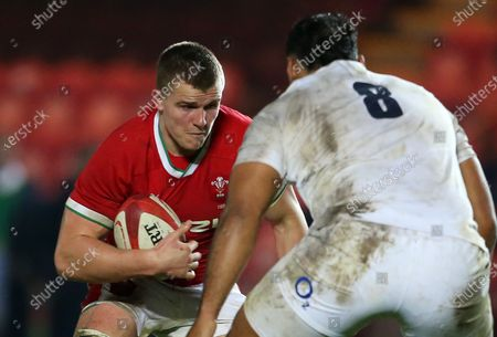 Shane Lewis-Hughes of Wales is challenged by Billy Vunipola of England.