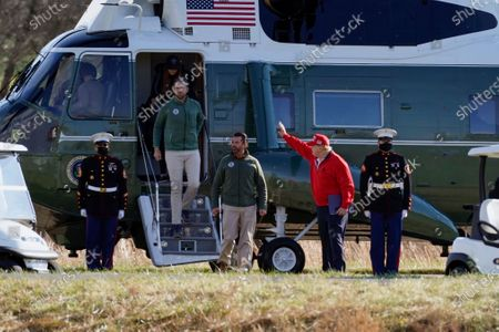 President Donald Trump waves as Donald Trump Jr., Eric Trump and Kimberly Guilfoyle get off Marine One after it landed at Trump National Golf Club, in Sterling, Va
