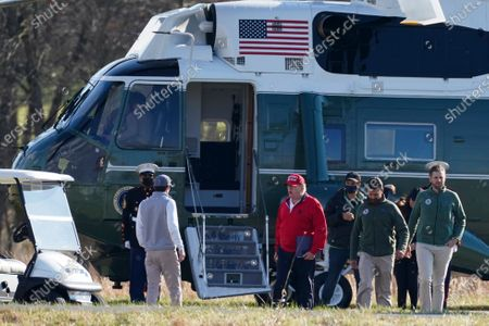 President Donald Trump walks with Donald Trump Jr., Eric Trump and Kimberly Guilfoyle after they exited Marine One at Trump National Golf Club, in Sterling, Va