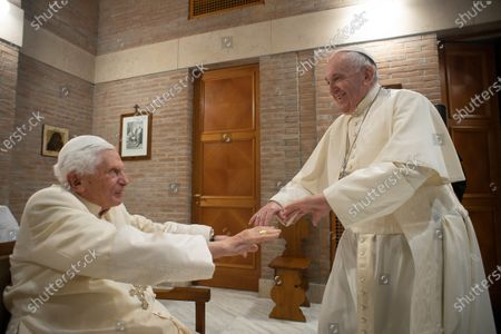Pope Francis hold hands with Pope Emeritus Benedict XVI as he pays him a visit after the Consistory, with the 13 newly elevated Cardinals, at the Vatican
