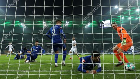 Stock Image of Schalke players Matija Nastasic (C), Omar Mascarell (bottom) and goalkeeper Frederik Ronnow (R) concede Moenchengladbach's 1-0 lead during the German Bundesliga soccer match between Borussia Moenchengladbach and FC Schalke 04 at Borussia-Park in Moenchengladbach, Germany, 28 November 2020.