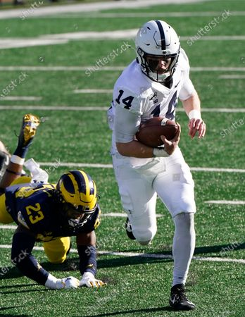 Penn State quarterback Sean Clifford pulls away from Michigan linebacker Michael Barrett (23), for a 28-yard touchdown during the first half of an NCAA college football game, in Ann Arbor, Mich