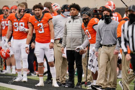 Oklahoma State running back Chuba Hubbard, center, watches from the sidelines wearing a boot on his right foot during an NCAA college football game against Texas Tech in Stillwater, Okla., . From the left are Braden Cassity (90), Spencer Sanders (3), Hubbard, LD Brown (0), and head coach Mike Gundy