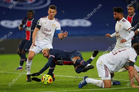 PSG's Neymar falls as he challenges for the ball with Laurent Koscielny of Bordeaux, left, and Otavio of Bordeaux, right, during their League One soccer match between Paris Saint Germain and Bordeaux, at the Parc des Princes stadium in Paris, France