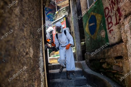 Volunteers spray disinfectant in an alley to help contain the spread of the new coronavirus, at the Santa Marta slum in Rio de Janeiro, Brazil, . Volunteers who have been sanitizing the narrow alleyways and homes in the shantytowns in Rio provided this service for the last time on Saturday. The volunteers lead by Thiago Firmino, who works as a tourist guide in the favela, say they have run out funds even as number of COVID-19 infections are spiking again in the city