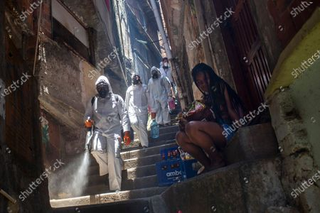 Volunteers spray disinfectant in an alley to help contain the spread of the new coronavirus, at the Santa Marta slum in Rio de Janeiro, Brazil, . Volunteers who have been sanitizing the narrow alleyways and homes in the shantytowns in Rio provided this service for the last time on Saturday. The volunteers led by Thiago Firmino, who works as a tourist guide in the favela, say they have run out funds even as number of COVID-19 infections are spiking again in the city