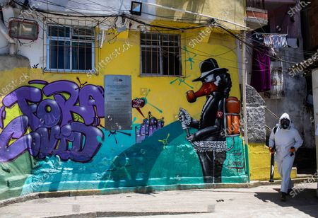 """Thiago Firmino, 39, sprays disinfectant to help contain the spread of the new coronavirus, next to a mural depicting the late Michael Jackson with a message that reads in Portuguese: """"Get out COVID"""", at the Santa Marta slum, in Rio de Janeiro, Brazil, . Volunteers who have been sanitizing the narrow alleyways and homes in the shantytowns in Rio provided this service for the last time on Saturday. The volunteers led by Firmino, who works as a tourist guide in the favela, say they have run out funds even as number of COVID-19 infections are spiking again in the city"""