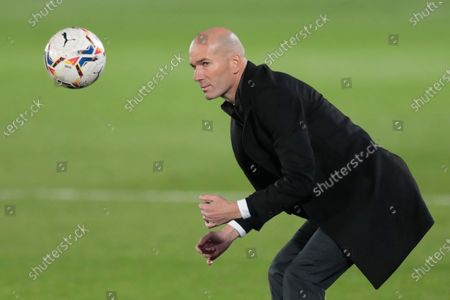 Real Madrid's head coach Zinedine Zidane eyes a ball during the Spanish La Liga soccer match between Real Madrid and Alaves at Alfredo di Stefano stadium in Madrid, Spain