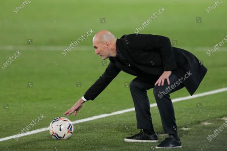Real Madrid's head coach Zinedine Zidane touches a ball during the Spanish La Liga soccer match between Real Madrid and Alaves at Alfredo di Stefano stadium in Madrid, Spain
