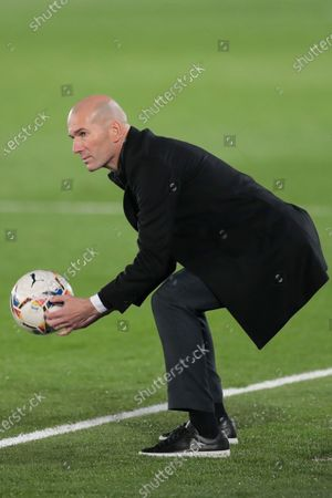 Real Madrid's head coach Zinedine Zidane holds a ball during the Spanish La Liga soccer match between Real Madrid and Alaves at Alfredo di Stefano stadium in Madrid, Spain