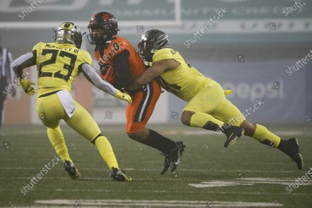 Oregon State wide receiver Trevon Bradford (8) is taken down by Oregon's Isaac Slade-Matautia and Verone McKinley III (23) during an NCAA college football game in Corvallis, Ore., . Oregon State won 41-38