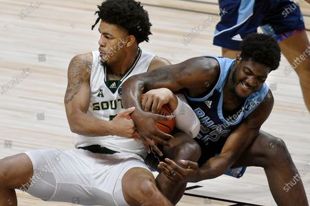 Stock Image of South Florida's David Collins, left, and Rhode Island's Makhel Mitchell vie for control of the ball during the first half of an NCAA college basketball game, in Uncasville, Conn