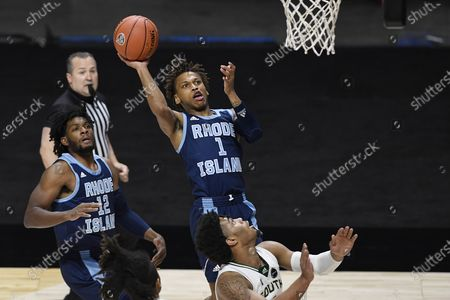 Stock Photo of Rhode Island's Fatts Russell shoots as South Florida's David Collins, lower right, defends during the first half of an NCAA college basketball game, in Uncasville, Conn