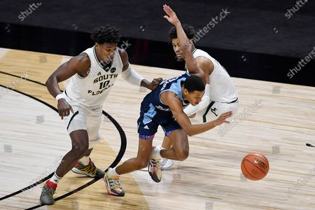 Rhode Island's Jeremy Sheppard, center, picks off the ball between South Florida's Alexis Yetna, left, and David Collins during the first half of an NCAA college basketball game, in Uncasville, Conn