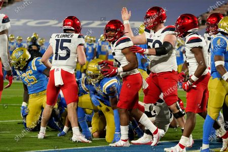 Arizona running back Michael Wiley, center with ball, celebrates his rushing touchdown against UCLA during the first half of an NCAA college football game, in Pasadena, Calif