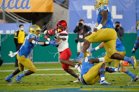 Arizona running back Michael Wiley, second from left, runs next to UCLA defensive back Elisha Guidry (30) during the first half of an NCAA college football game, in Pasadena, Calif
