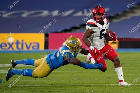 Arizona running back Michael Wiley (6) runs as UCLA linebacker Mitchell Agude (45) makes a tackle during the second half of an NCAA college football game, in Pasadena, Calif