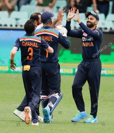 India's Virat Kohli, right, is congratulated by teammates after taking a catch to dismiss Australia's Aaron Finch during the one day international cricket match between India and Australia at the Sydney Cricket Ground in Sydney, Australia