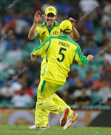 Australia's Moises Henriques, left, is congratulated by teammate Aaron Finch after taking a catch to dismiss India's Virat Kohli during the one day international cricket match between India and Australia at the Sydney Cricket Ground in Sydney, Australia