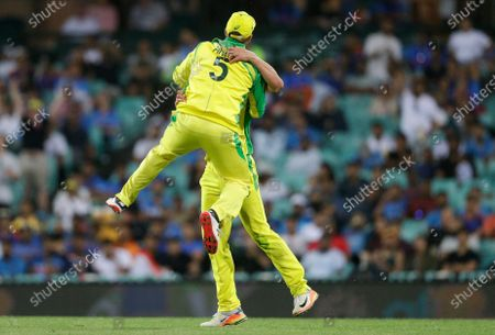 Australia's Moises Henriques is congratulated by teammate Aaron Finch after taking a catch to dismiss India's Virat Kohli during the one day international cricket match between India and Australia at the Sydney Cricket Ground in Sydney, Australia