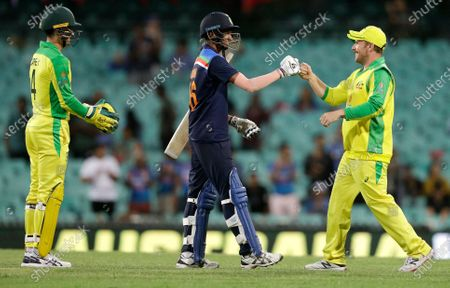 India's Navdeep Saini, centre, gestures with Australia's Aaron Finch, right, following the one day international cricket match between India and Australia at the Sydney Cricket Ground in Sydney, Australia