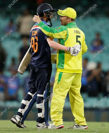 Australia's Aaron Finch, right, and India's Navdeep Saini embrace following the one day international cricket match between India and Australia at the Sydney Cricket Ground in Sydney, Australia