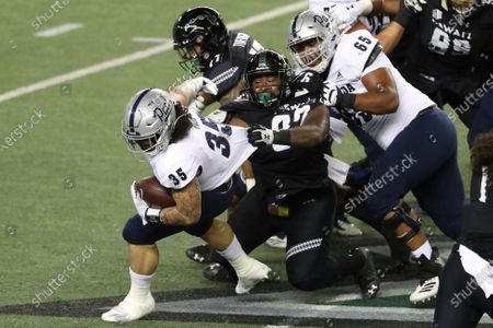 Stock Image of Nevada offensive lineman Aaron Frost (65) tries to keep Hawaii defensive lineman Zach Ritner (97) from pulling down Nevada running back Toa Taua (35) during an NCAA college football game, in Honolulu