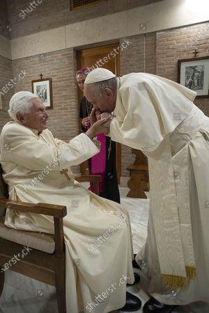 Pope Francis hold hands with Pope Emeritus Pope Benedict XVI