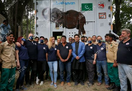 Pakistani wildlife workers, officials and experts from the international animal welfare organization Four Paws, pose for photograph next to a crate holding an elephant named Kaavan before he is transported to a sanctuary in Cambodia, at the Marghazar Zoo in Islamabad, Pakistan, . Kavaan, the world's loneliest elephant, became a cause celebre in part because America's iconic singer and actress Cher joined the battle to save him from his desperate conditions at the zoo