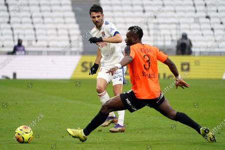 Lyon's Leo Dubois, left, challenges for the ball with Reims' Ghislain Konan during the French League One soccer match between Lyon and Reims in Decines, near Lyon, central France