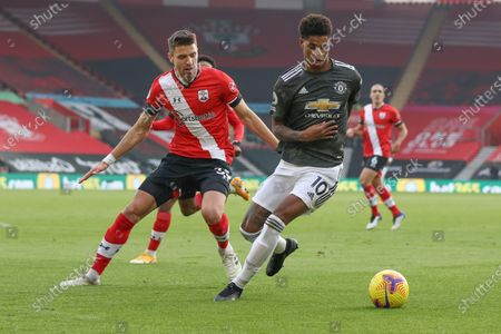 Manchester United's Marcus Rashford, right, and Southampton's Jan Bednarek go for the ball during an English Premier League soccer match between Southampton and Manchester United at the St. Mary's stadium in Southampton, England