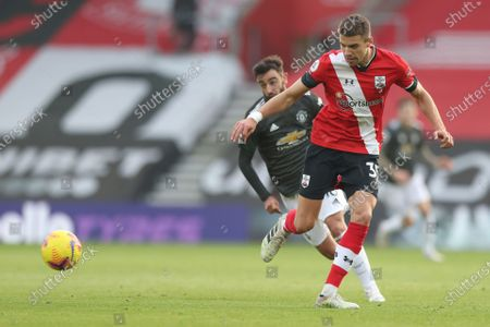 Southampton's Jan Bednarek is challenged by Manchester United's Bruno Fernandes during an English Premier League soccer match between Southampton and Manchester United at the St. Mary's stadium in Southampton, England