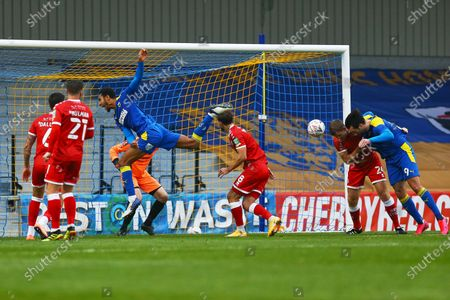 Crawley defend their goal as Terell Thomas of AFC Wimbledon fly's though air while Tony Craig of Crawley Town grapples with Ollie Palmer (right) of AFC Wimbledon  during AFC Wimbledon vs Crawley Town, Emirates FA Cup Football at Plough Lane on 29th November 2020
