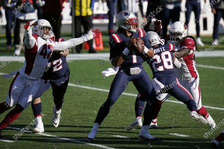 New England Patriots quarterback Cam Newton drops back to pass under pressure from Arizona Cardinals linebacker Devon Kennard, left, in the first half of an NFL football game, in Foxborough, Mass