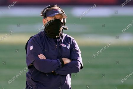 New England Patriots head coach Bill Belichick wears a protective mask during the coronavirus pandemic as he watches from the sideline in the first half of an NFL football game against the Arizona Cardinals, in Foxborough, Mass