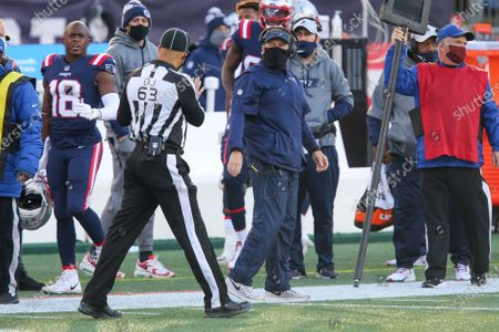 New England Patriots head coach Bill Belichick talks with down judge Mike Carr (63) during the second half of an NFL football game against the Arizona Cardinals, in Foxborough, Mass