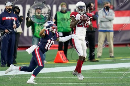 Arizona Cardinals cornerback Dre Kirkpatrick, right, intercepts a pass intended for New England Patriots wide receiver Damiere Byrd, left, in the second half of an NFL football game, in Foxborough, Mass