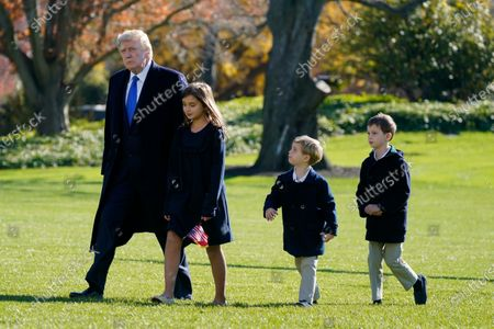 President Donald Trump walks with his grandchildren Arabella Kushner, Theodore Kushner and Joseph Kushner on the South Lawn of the White House in Washington, after stepping off Marine One. President Trump is returning from Camp David