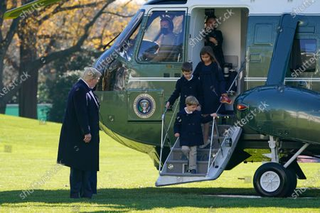 President Donald Trump watches as his grandchildren Theodore Kushner, Joseph Kushner and Arabella Kushner step off Marine One on the South Lawn of the White House in Washington, . President Trump is returning from Camp David