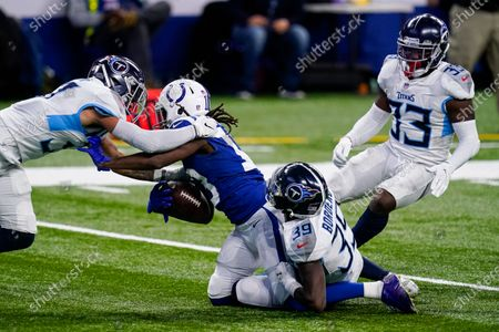Indianapolis Colts wide receiver T.Y. Hilton (13) is tackled by Tennessee Titans defensive back Chris Jackson (35) and strong safety Amani Hooker (37) in the second half of an NFL football game in Indianapolis