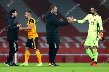 Wolverhampton Wanderers' head coach Nuno Espirito Santo shakes hands with his goalkeeper Rui Patricio, right, following the English Premier League soccer match between Arsenal and Wolverhampton Wanderers at Emirates Stadium, London