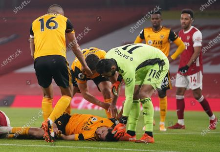 Raul Jimenez of Wolverhampton (C) receives help after a head-on collision during the English Premier League soccer match between Arsenal FC and Wolverhampton Wanderers in London, Britain, 29 November 2020.