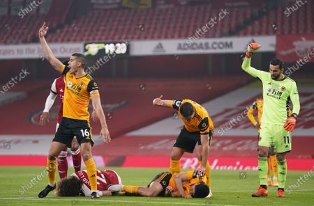 Players gesture for help after David Luiz of Arsenal (L) and Raul Jimenez of Wolverhampton (R) head clashed during the English Premier League soccer match between Arsenal FC and Wolverhampton Wanderers in London, Britain, 29 November 2020.