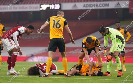 David Luiz of Arsenal (L) and Raul Jimenez of Wolverhampton (R) receive help after a head-on collision during the English Premier League soccer match between Arsenal FC and Wolverhampton Wanderers in London, Britain, 29 November 2020.