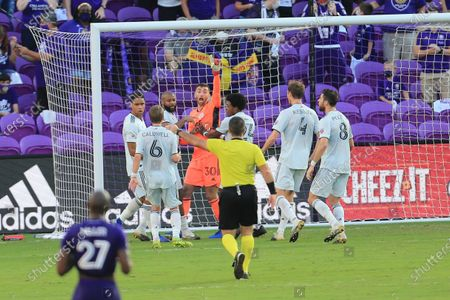 New England Revolution goalkeeper Matt Turner (30) celebrates with teammates after making a save on a penalty kick by Orlando City forward Nani (not shown) during the second half of an MLS playoff soccer match, in Orlando, Fla