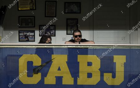 Dalma Maradona, left, daughter of Diego Maradona, sits in her father's box during a local tournament match between Boca Juniors and Newell's Old Boys at the Alberto J. Armando stadium in Buenos Aires, Argentina, . The Argentine soccer great died from a heart attack at his home Wednesday, Nov. 25, at the age of 60